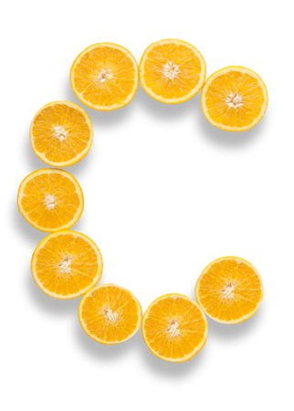 Vitamin C letter made from orange halves over a white background
