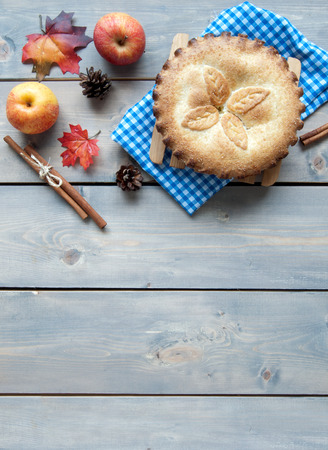cinammon: Apple pie with fruit ingredients autumn leaves and cinammon sticks on a wooden table