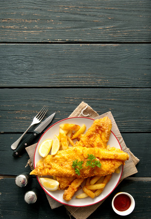 Two pieces of battered fish on a plate with chips Фото со стока