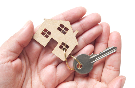 hands holding house: Hands holding a miniature house attached to key ring, property real estate concept