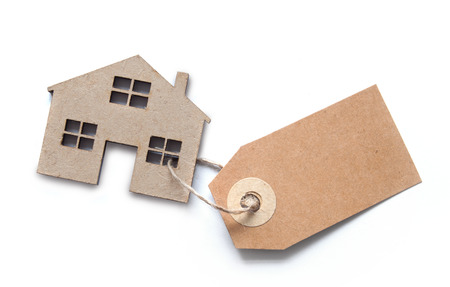 blank tag: Label attached to miniature house over a white background Stock Photo