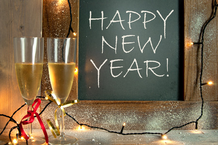 next year: Champagne glasses next to chalkboard with happy new year greeting