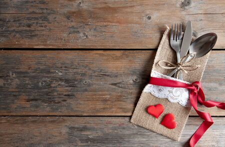 cuchara: Cutlery set inside pouch with two red hearts and silk ribbon over a wooden background Foto de archivo