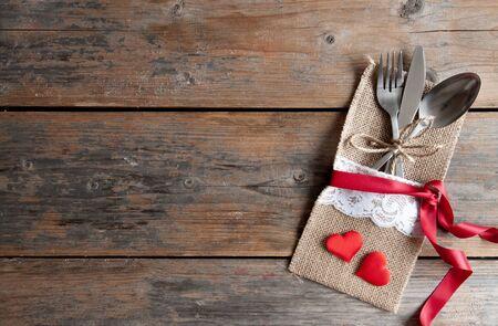 cuchara: Juego de cubiertos dentro de la bolsa con cinta de seda dos corazones rojos y sobre un fondo de madera Foto de archivo