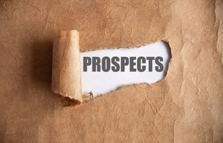 uncovering: Torn piece of scroll uncovering prospects underneath Stock Photo
