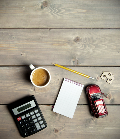 money and saving: Blank notepad on a wooden table with a miniature car and house