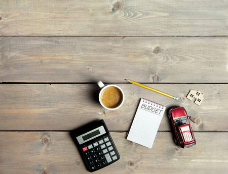 予算のミニチュアの車と家のシンボルと木製のテーブルの上に手書きでメモ帳