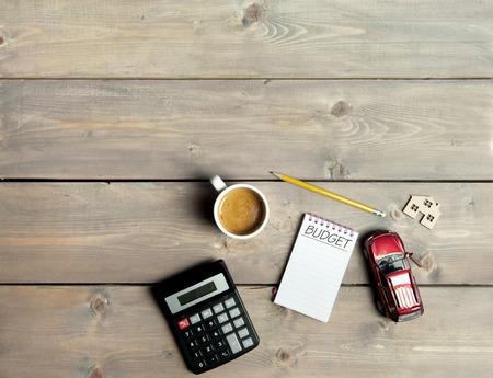 Bloc de notas con el presupuesto escrito a mano en la parte superior de una mesa de madera con un coche en miniatura y el símbolo de la casa Foto de archivo