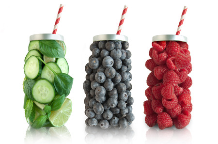 Smoothies in the shape of a beverage with straw including raspberries, blueberries and vegetables Stock Photo