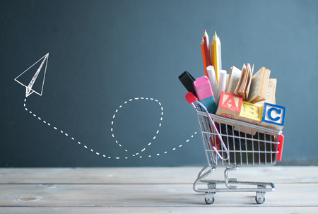 Shopping cart filled with stationery next to a chalkboard with a paper airplane sketch Stock Photo
