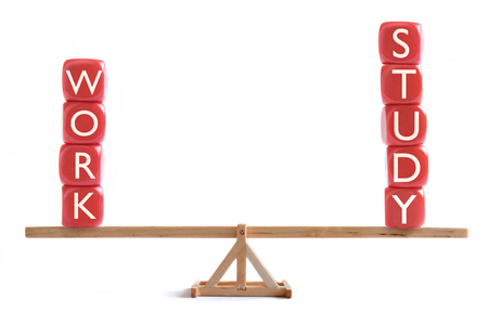 Seesaw balancing work and study block letters Stock Photo