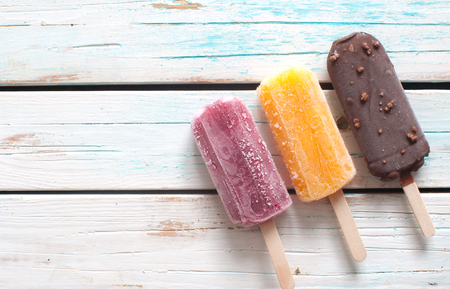 Assorted flavored ice lollies over a wooden background