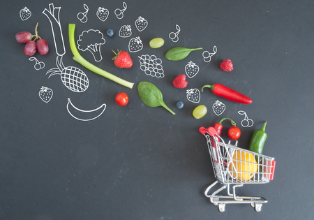 Grocery shopping cart filled with fruits and vegetables and sketches on a chalkboard