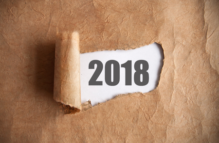 Torn piece of scroll uncovering 2018  underneath Stock Photo