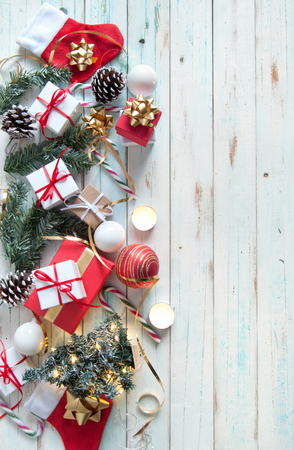 Christmas gifts and decorations with candles on a wooden background
