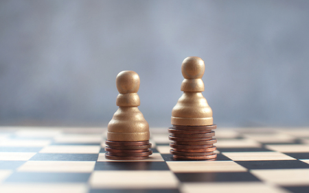 Two chess pawns with on top of a heap of coins