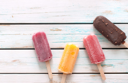 Various flavored ice popsicles over wooden background Stock Photo