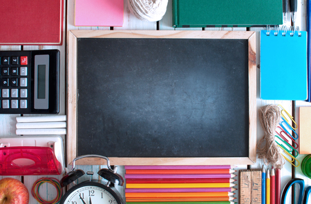 Top view of various stationery objects with blackboard in the centre