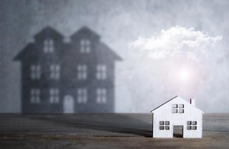Schaduw van een groot huis vanuit een miniatuurwoning Stockfoto