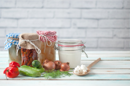 Naturally fermented foods in jars including kefir, gherkins and peppers and onions Banco de Imagens