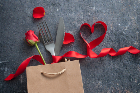 Fork and knife inside a gift bag with red ribbon heart Standard-Bild - 117502856