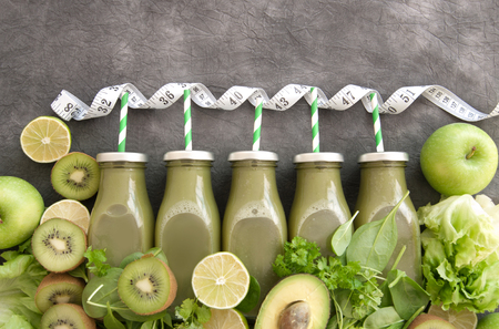 Healthy green bottled smoothies with straws and fresh ingredients and a measuring tape Standard-Bild - 117502857