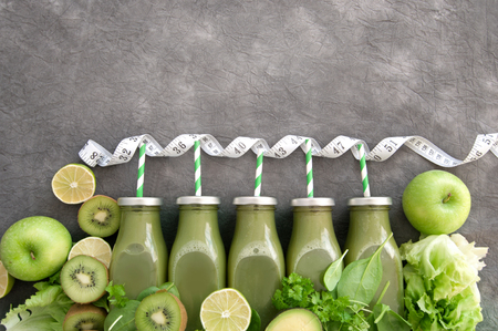 Row of green bottled smoothies with straws and fresh ingredients and a measuring tape Standard-Bild - 117502858