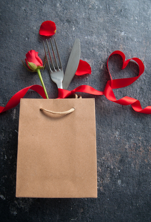Fork and knife inside a gift bag with red ribbon heart Standard-Bild - 117502860