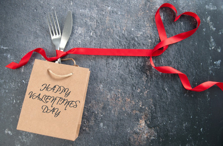Cutlery inside a gift bag with red ribbon heart Standard-Bild - 117502862