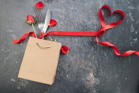Valentines gift bag with cutlery and heart shape ribbon Standard-Bild - 117502865