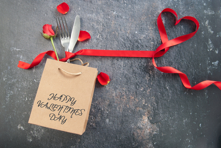 Cutlery inside a gift bag with red ribbon heart Standard-Bild - 117502868