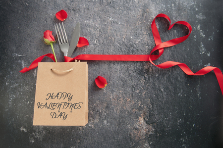 Cutlery inside a gift bag with red ribbon heart Standard-Bild - 117502869