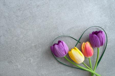 Seasonal tulips inside a heartshape grass blade Standard-Bild - 119056728