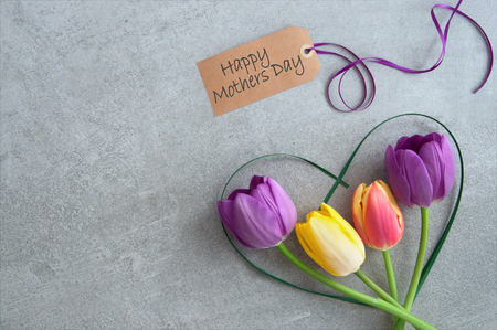 Mothers day greeting with spring tulips inside a heart shape grass stem Standard-Bild - 119056737