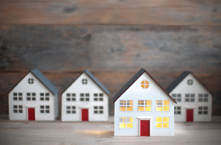 Miniature house with lights on standing out against a row of houses Standard-Bild - 121547769