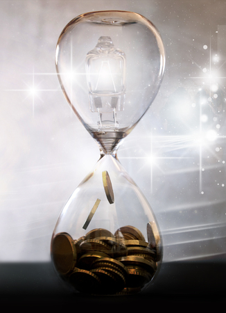 Light bulb inside an hourglass turning into money Standard-Bild - 121547770