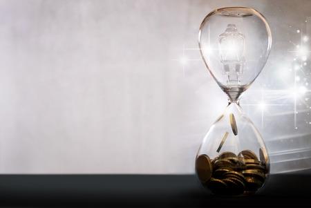 Light bulb inside an hourglass turning into cash Standard-Bild - 121761600