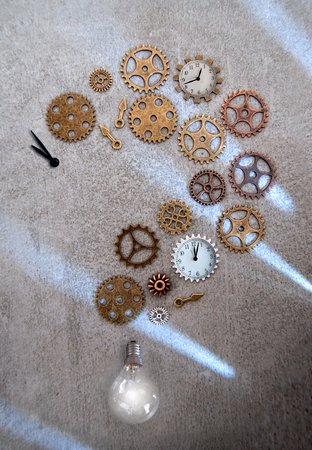 Clock parts including hands gears and cogs in the shape of a question mark with light bulb Standard-Bild - 121761601
