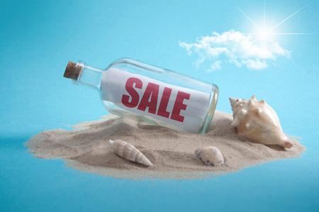 Sale sign inside a message bottle on a sandy island