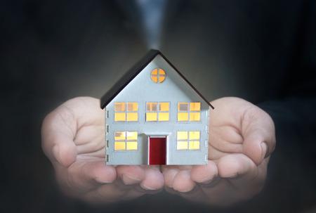 Business man holding a model house Standard-Bild - 124679921