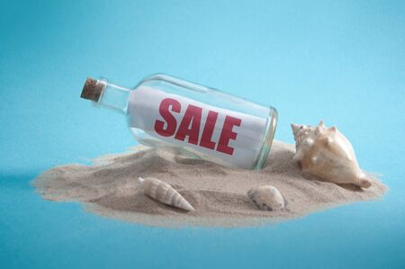 Sale sign inside a message bottle on a sandy island Standard-Bild - 124679952