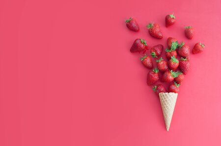 Strawberries falling out of an ice cream cone Standard-Bild - 124679990