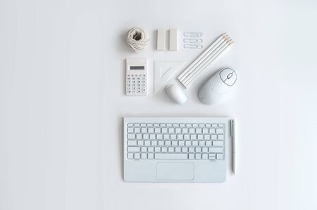 Minimalist desktop view of stationery supplies including pencils, calculator, keyboard and computer mouse
