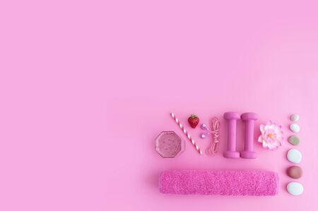 Health and excercise still life, including dumbbells, towel, and a berry smoothie with straw on a pink background