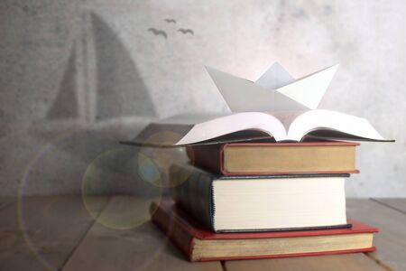 Paper boat on books with shadow of a sail boat, dreams, potential, learning concept Stockfoto - 129170750