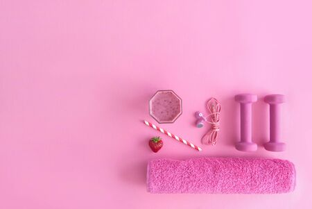 Health and excercise accessories, including dumbbells, towel, and a berry smoothie with straw on a pink background