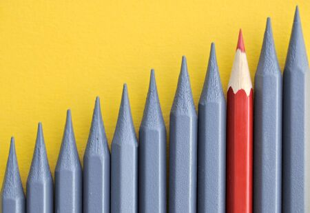 Red pencil amongst greyed out pencils conceptual
