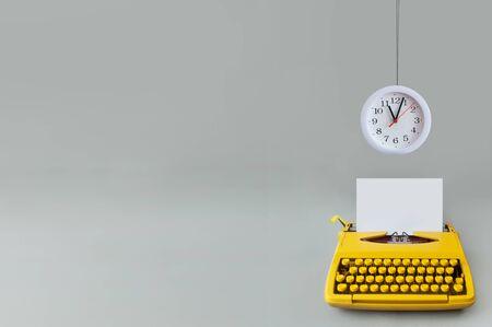 Clock hanging over a retro typewriter