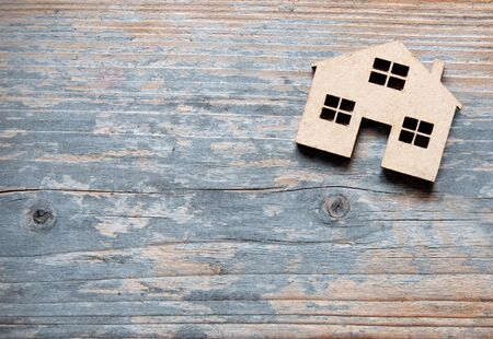 Small miniature house over a wooden background with space Фото со стока - 131322811