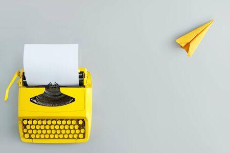 Máquina de escribir retro con avión de papel amarillo, inspiración e innovación